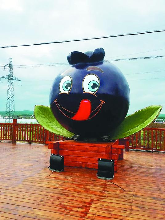 蓝莓产业园前可爱的蓝莓卡通形象.本报记者桑蕾摄
